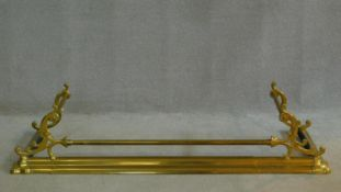 A 19th century brass adjustable fire kerb decorated with floral scrollwork. H.27 W.154 D.43cm (fully