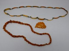 A collection of amber and ivory jewellery. Including an amber leaf brooch, a graduated amber chip
