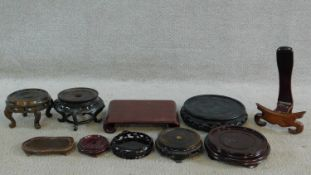 A miscellaneous collection of ten Chinese carved and pierced hardwood urn and plate stands. H.