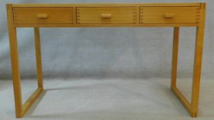 A contemporary light oak writing table fitted with three frieze drawers on trestle style base. H.