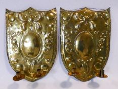 A pair of 18th century Dutch brass shield shaped twin candle wall sconces with repousse