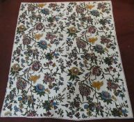 A large crewel work embroidered throw with brightly coloured flowers on a cream background with