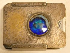 A Liberty Tudric style hammered pewter playing card case with iridescent blue enamel central roundel