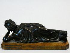 An antique bronze reclining Buddha mounted on an oak plinth. H.11 W.26 D.10cm