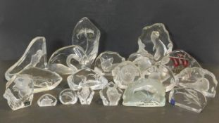 An extensive collection of glass paper weights each with various carved animals, boats and flowers.