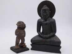 An Carved Eastern hardwood figure of the seated Buddha and a clay carving of an African tribal