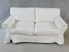 A contemporary two seater sofa in calico loose cover. H.90 W.170 D.83cm