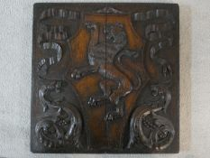 A 19th century carved oak heraldic panel depicting a Lion Rampant on a shaped shield surrounded by