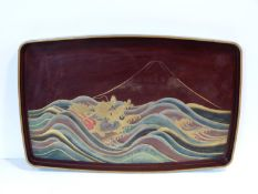 A Meiji period Japanese gilded lacquered painted tray. Depicting a dragon among the waves with Mount