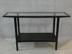 A tubular metal framed console table with inset plate glass top and fitted with undertier. H.75xW.