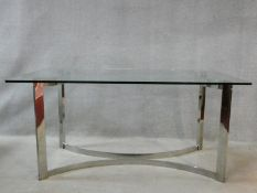 A vintage dining table in the style of Gavina, the heavy plate glass top resting on a shaped