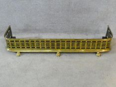 A 19th century brass fire fender with pierced grille decoration on lion's paw feet. H.20xW.113xL.