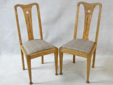 A pair of Arts and Crafts elm dining chairs with pierced splat backs and drop in seats on square