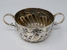 A two handled Victorian repousse design silver porriger with floral design and scrolling handles.