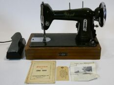 A vintage cased sewing machine with maker's and retailer's labels and with original papers and