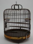 A vintage Oriental wooden bird cage with two ceramic water feeders with cherry blossom design and