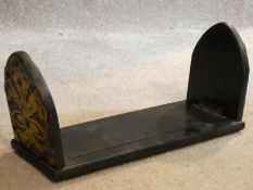 A Victorian ebonised desk top book slide with engraved pierced brass bound arched ends. 33x13cm