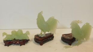 A Chinese carved jade figure of a pair of dogs on carved and pierced hardwood base and two similar
