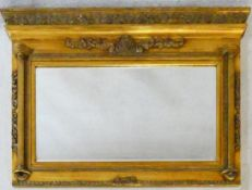 A Regency style gilt framed overmantel mirror with architectural pediment above bevelled plate
