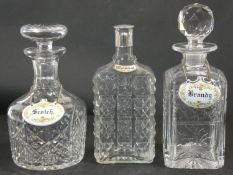 Three cut crystal drinks decanters, two with stoppers and one with a silver plated top, each with