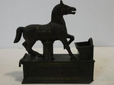 A vintage 'Trick Pony' cold painted cast iron novelty moving money box in the form of a horse