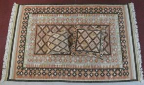 A Kilim with central repeating diamond design within broad double geometric borders along with two