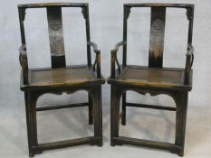 A pair of mid century Chinese hardwood armchairs with carved character marks to the back splats