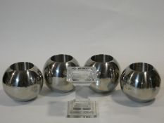 A set of four chrome spherical candle holders and a glass pedestal candle holder. H.14xW.10xL.10cm