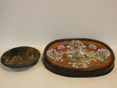 A Japanese black lacquered shallow bowl with gilt decoration showing figures in a court setting