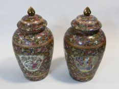 A pair of Chinese Famille Rose porcelain lidded temple jars, panels with village scenes. Qianlong