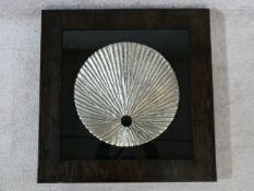 A contemporary carved wood textured silver disk, mounted on black, shadow box framed. 80x80cm