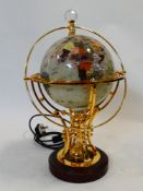 An electric marble chip inlaid acrylic globe on gilt metal stand with remote control for three