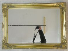 A contemporary wall mirror in scrolling gilt frame. 65x90cm