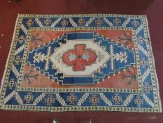 A Shirvan carpet with central lozenge medallion on burgundy field within stylised geometric triple