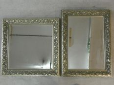 A bevelled glass wall mirror in silvered floral frame and a similar wall mirror. H.91 W.68cm (