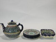 An Uzbec glazed and hand painted colourful ceramic tea set; tea pot, four side plates and a pair