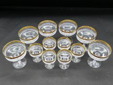 A set of six moulded glass and gilt rimmed champagne coupes and a similar smaller set. H.11 D.9cm (
