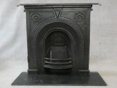 An ornately cast 19th century iron fire surround, mantel shelf and insert with grate on marble