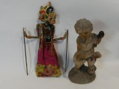 A painted Indonesian stick puppet and a carving of a child seated on a tree stump. H.51cm