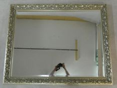 A bevelled glass wall mirror in silvered Art Nouveau style flowing floral design frame. H.135 W.