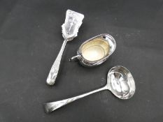 Three silver plated items; a pair of engraved asparagus tongs, a ladle and a milk jug. L.27cm