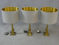 A set of three contemporary Corinthian column brass table lamps with shades. H.69xD.41cm
