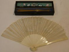 A Japanese carved bone fan with silk embroidered dragon design in fitted lacquered box with
