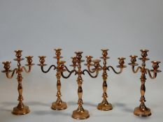 A collection of five copper effect metal three branch table candelabras. H.40cm