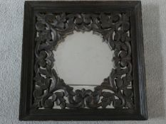 An Eastern teak wall mirror with carved and pierced inner frame. 40x40cm