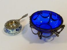 A Dutch repousse floral design pierced silver tea strainer with white and blue ceramic bowl, along