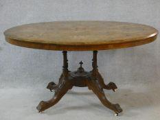 A Victorian burr walnut, satinwood and ebony inlaid tilt top dining table on quadruple turned