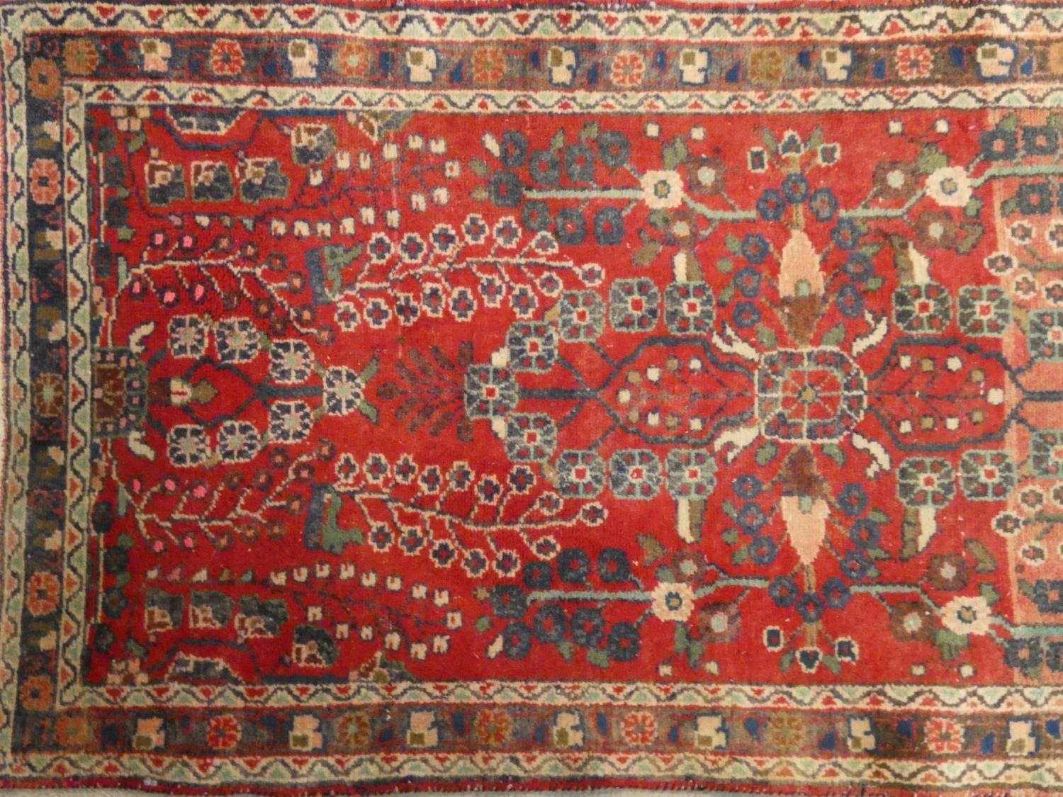 An Eastern runner with repeating floral medallions on a madder field within stylised multiple - Image 2 of 5