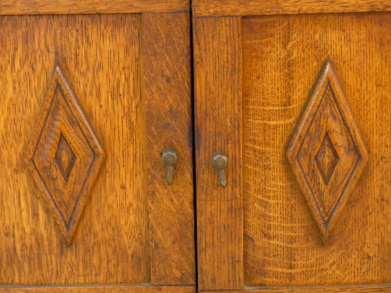 An early 20th century country oak style side cabinet with carved panel doors on squat square - Image 7 of 14