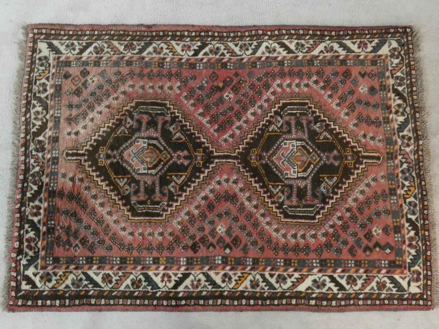 An Eastern rug with double stepped lozenge medallions on a blush ground within stylised floral